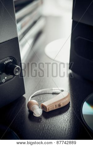 Vintage Stylized Photo Of Hearing Aid And Music Speaker.