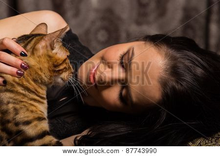 Young beautiful brunette holding a Bengal cat, dark bedroom.