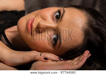 Portrait of a beautiful young brunette woman in a dark bedroom
