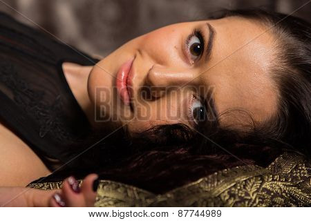 Portrait of a beautiful young brunette woman in a dark bedroom.