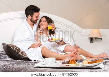 Young Couple On Honeymoon In Hotel Room.