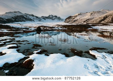 The scenic Vatnajokull National Park in the late afternoon, with snow covered mountains and volcanoes, and calm lakes reflecting the blue skies.