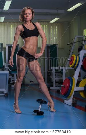 Sports, bodybuilding. Attractive woman in gym