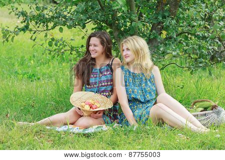 Blonde And Brunette Girls Sitting With Organic Farming Harvest