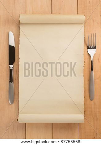 parchment and fork with knife on wooden background
