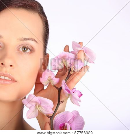 Beautiful Face Of Young Brunette Woman With Healthy Skin And Pink Orchid
