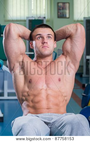 A man pumping abdominal muscles. Man in the gym
