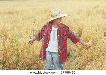 Portrait Of Teenage Farm Boy In Checkered Shirt And Wide-brimmed Straw Hat