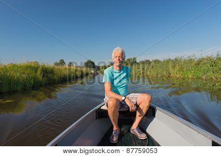 Senior man in motor boat in nature