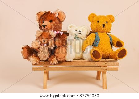 Stuffed vintage bears sitting on bench at beige background