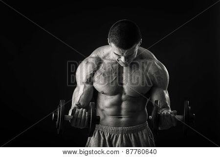 Handsome muscular man working out with dumbbells in gym. concept of a healthy lifestyle
