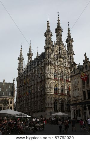 LEUVEN, BELGIUM - AUGUST 14, 2012: People walk in front of the Gothic Town Hall on the Grote Markt in Leuven, Flemish Brabant, Belgium.