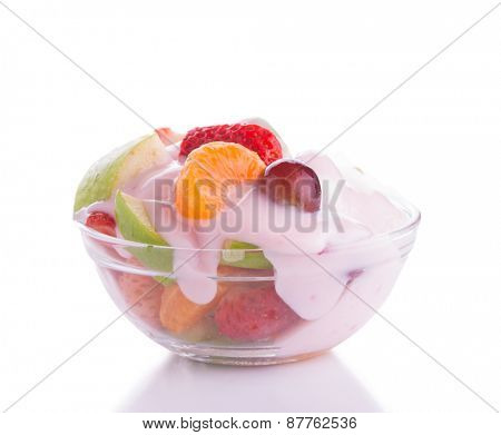 Colorful fruit salad in a glass bowl, topped with pink strawberry yogurt, on light background