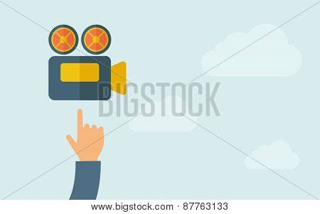 A hand pointing to video cam icon. A contemporary style with pastel palette, light blue cloudy sky background. Vector flat design illustration. Horizontal layout with text space on right part.