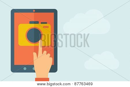 A hand is touching the screen of a tablet with camera icon. A contemporary style with pastel palette, light blue cloudy sky background. Vector flat design illustration. Horizontal layout with text