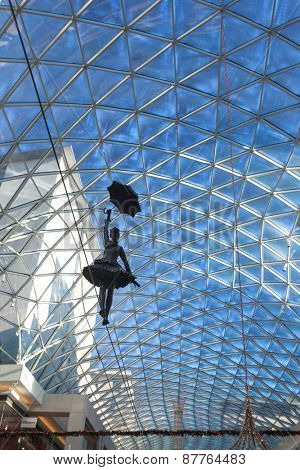BRATISLAVA, SLOVAKIA - JANUARY 6, 2015: Statue of girl walking on wire with open umbrella inside of Galleria Eurovea shopping centre.