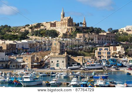MGARR, MALTA - JANUARY 13, 2015: Mgarr harbor with view on church to Our Lady of Lourdes on top of the hill.