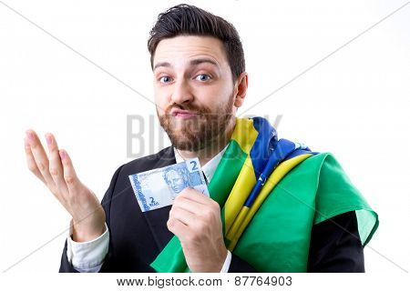 Brazilian not so happy holding Brazilian money and the flag of Brazil