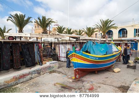 MARSAXLOKK, MALTA - JANUARY 11, 2015: Luzzu, traditional eye boat at Marsaxlokk market, one of the city's main features especially on sunday.