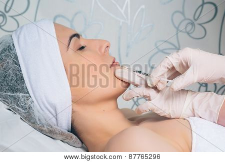 Closeup of woman getting cosmetic injection in the lips