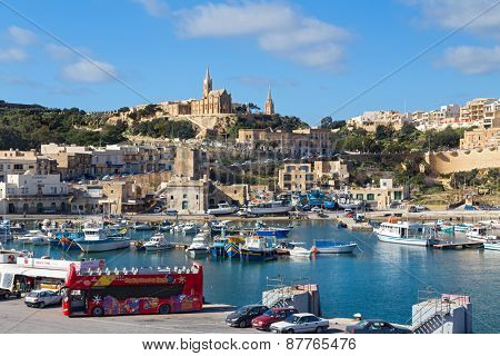MGARR, MALTA - JANUARY 13, 2015: Mgarr harbour with view of church Our Lady of Lourdes on top of the hill, Gozo island.