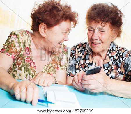 Two old women consider receipts. Female counts bill