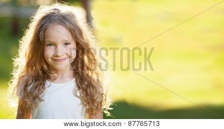 Happy laughing girl on grass. Smiling one child outdoors