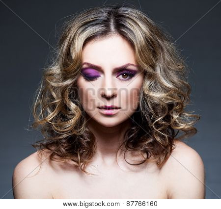 Beautiful mid woman with curly brown hair. Glamour female with purple makeup. Studio shot