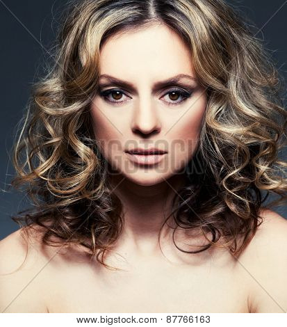 Beautiful mid woman with curly brown hair. Glamour smiling female. Studio shot