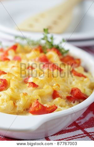 Macaroni and cheese with tomato in a baking dish. Selective focus