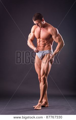 Bodybuilder posing on a black background