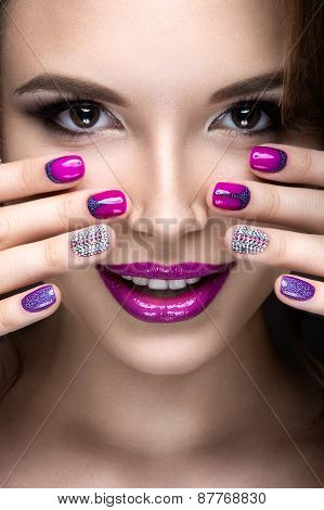 Beautiful girl with a bright evening make-up and manicure with rhinestones. Nail design.