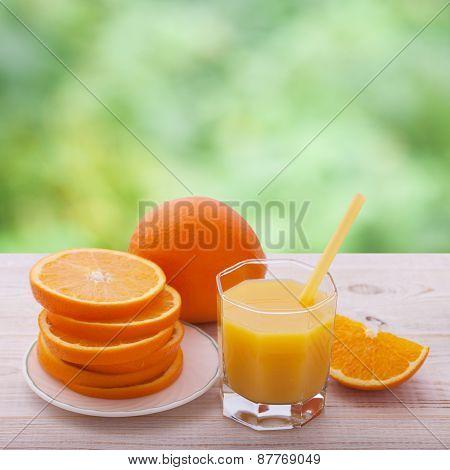Orange juice with sliced orange half on wooden table