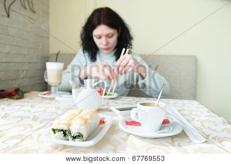 Woman eating sushi in an Asian restaurant