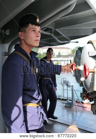 SEVASTOPOL, CRIMEA, UKRAINE - AUGUST 17, 2012: Seamen at the torpedo tubes on the Russian frigate
