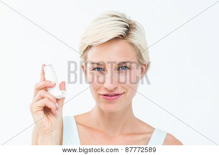 Pretty woman holding inhaler smiling at camera on white background