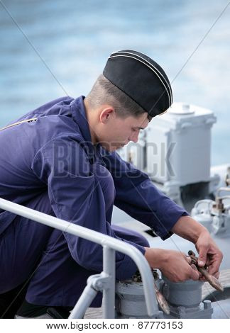 SEVASTOPOL, CRIMEA, UKRAINE - AUGUST 17, 2012: Seaman performs maintenance the torpedo tube on the Russian frigate