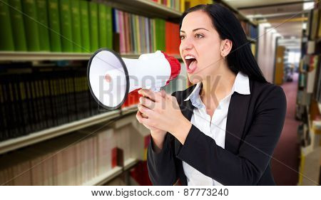Pretty businesswoman shouting with megaphone against rows of bookshelves in the library