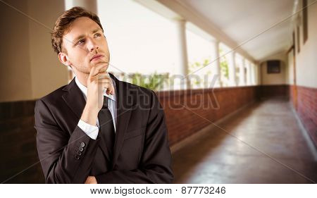 Young businessman thinking with hand on chin against hallway