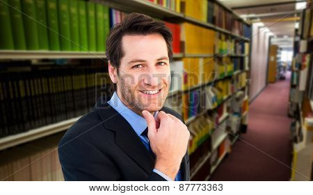 Businessman touching his chin while smiling at camera against rows of bookshelves in the library