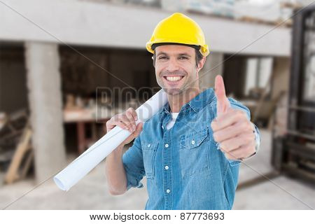 Architect holding blueprint while gesturing thumbs up against workshop