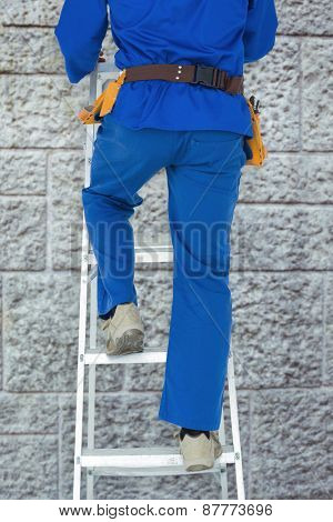 Low section of carpenter climbing step ladder against grey brick wall