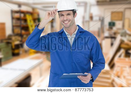 Happy supervisor wearing hard hat while holding clip board against workshop