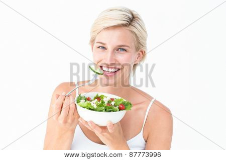 Beautiful blonde woman eating salad on white background