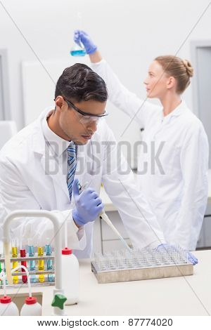 Scientists examining tubes and baker in the laboratory