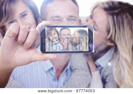 Hand holding smartphone showing against happy father carrying his son and his wife on his back