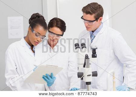 Scientists taking notes in laboratory