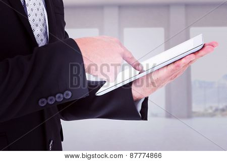 Businessman using his tablet pc against room overlooking ocean