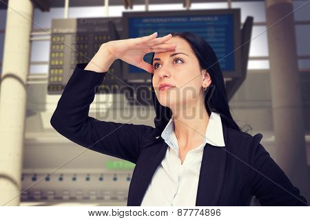Pretty businesswoman looking with hand up against airport