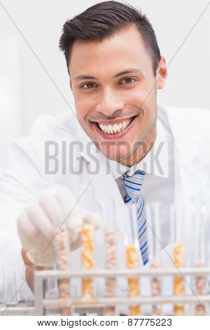 Happy scientist looking at camera with tubes of corn and kernel in the laboratory